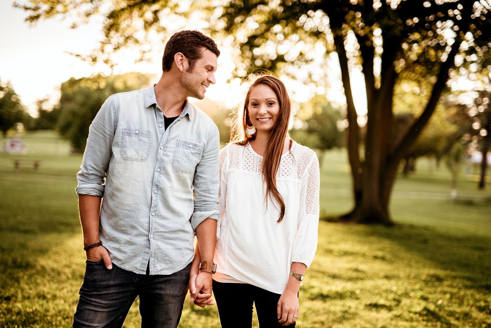 man holding hand of woman standing near tree